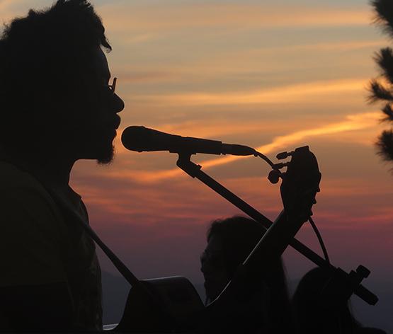Ao fundo da imagem, o sol se põe. No primeiro plano há sombra de um homem cantando e tocando violão.