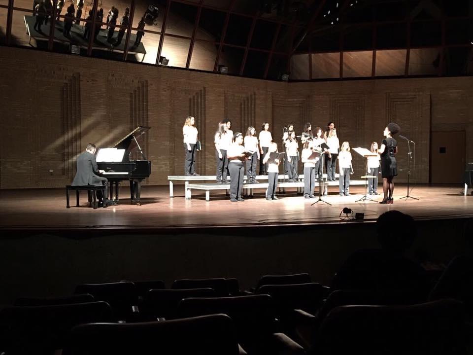 A imagem mostra um grupo de meninas no palco do Auditório Claudio Santoro. Elas cantam sob a regência de uma mulher alta. Um homem toca piano à esquerda.