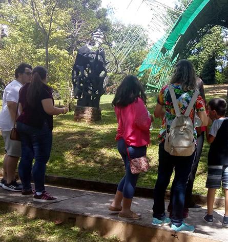 """A imagem mostra um grupo de visitantes caminhando pela fase """"Cruzes"""" de Felícia Leirner"""