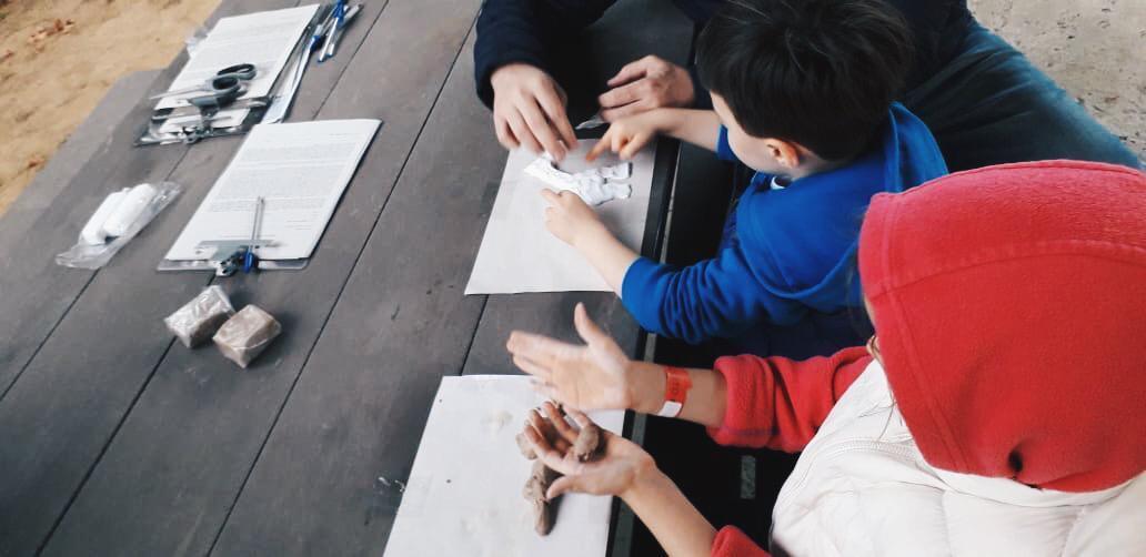 Duas crianças estão brincando com argila sobre uma mesa
