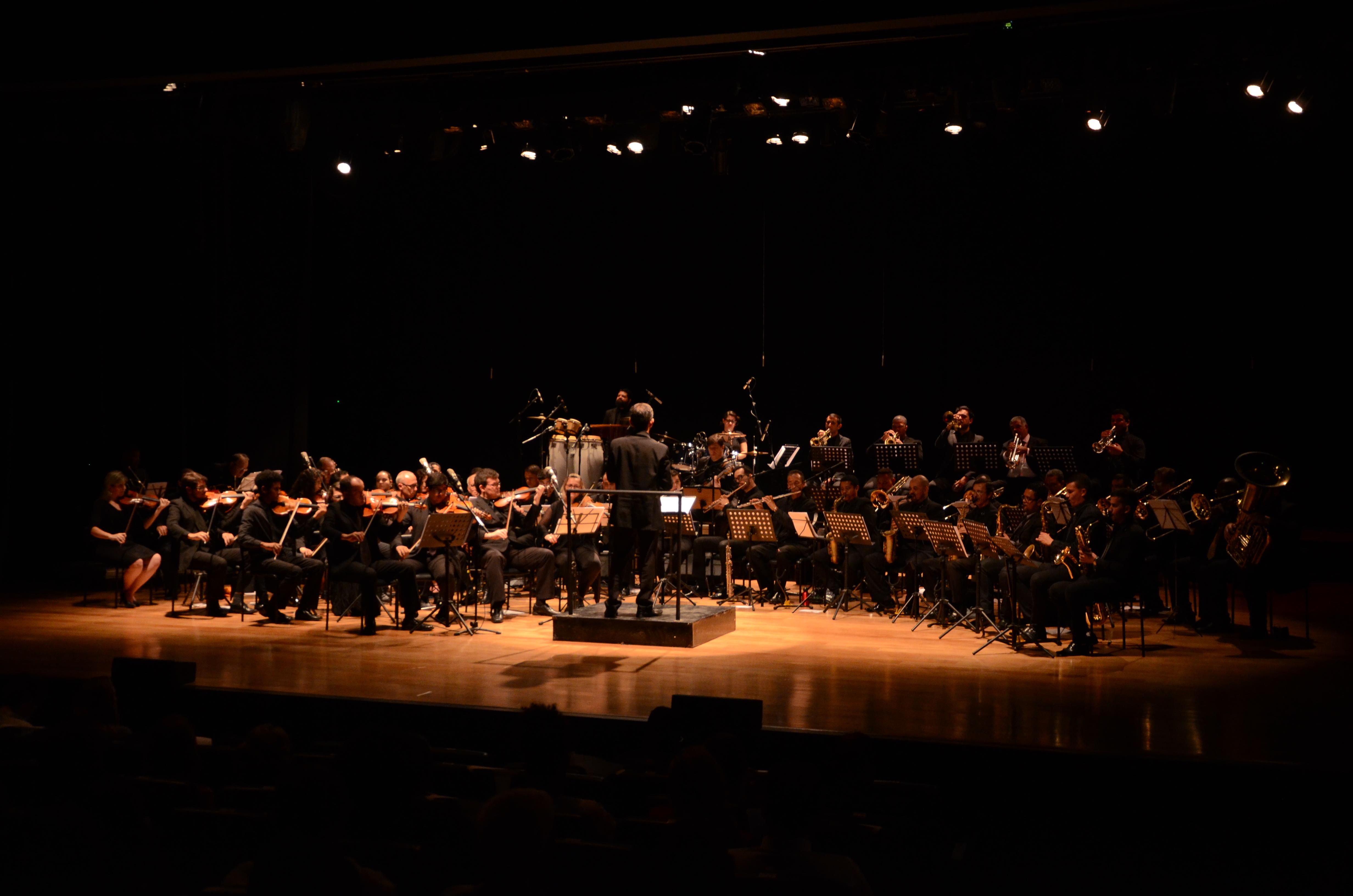 Orquestra se apresentando soba regência de um maestro