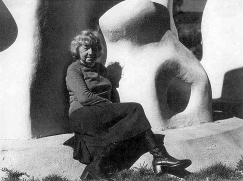 Felícia Leirner está sentada sobre a base de uma de suas esculturas.