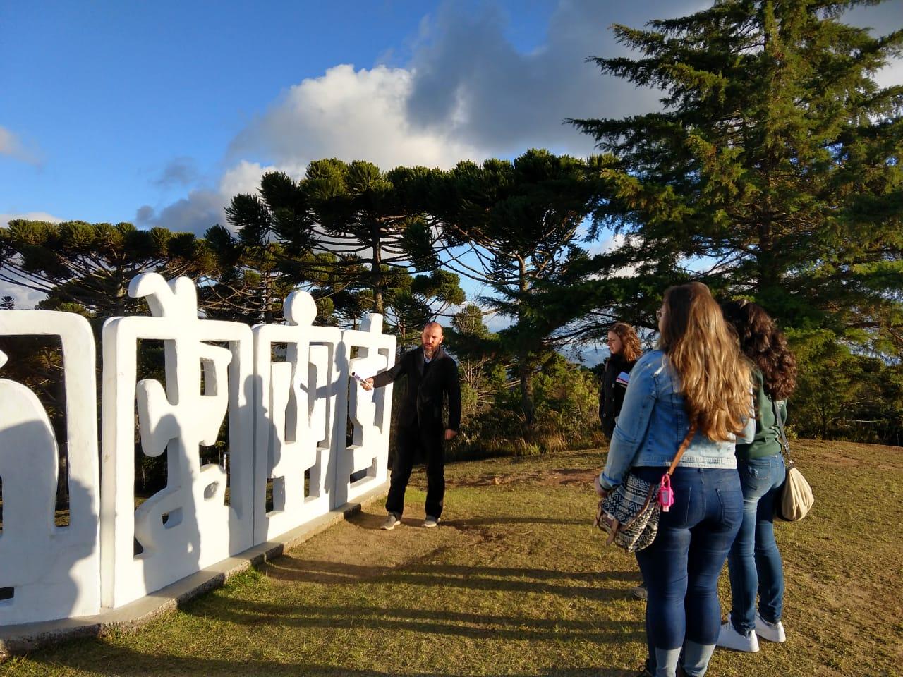Um educador explica as características da escultura Horizonte a um grupo pequeno de pessoas.