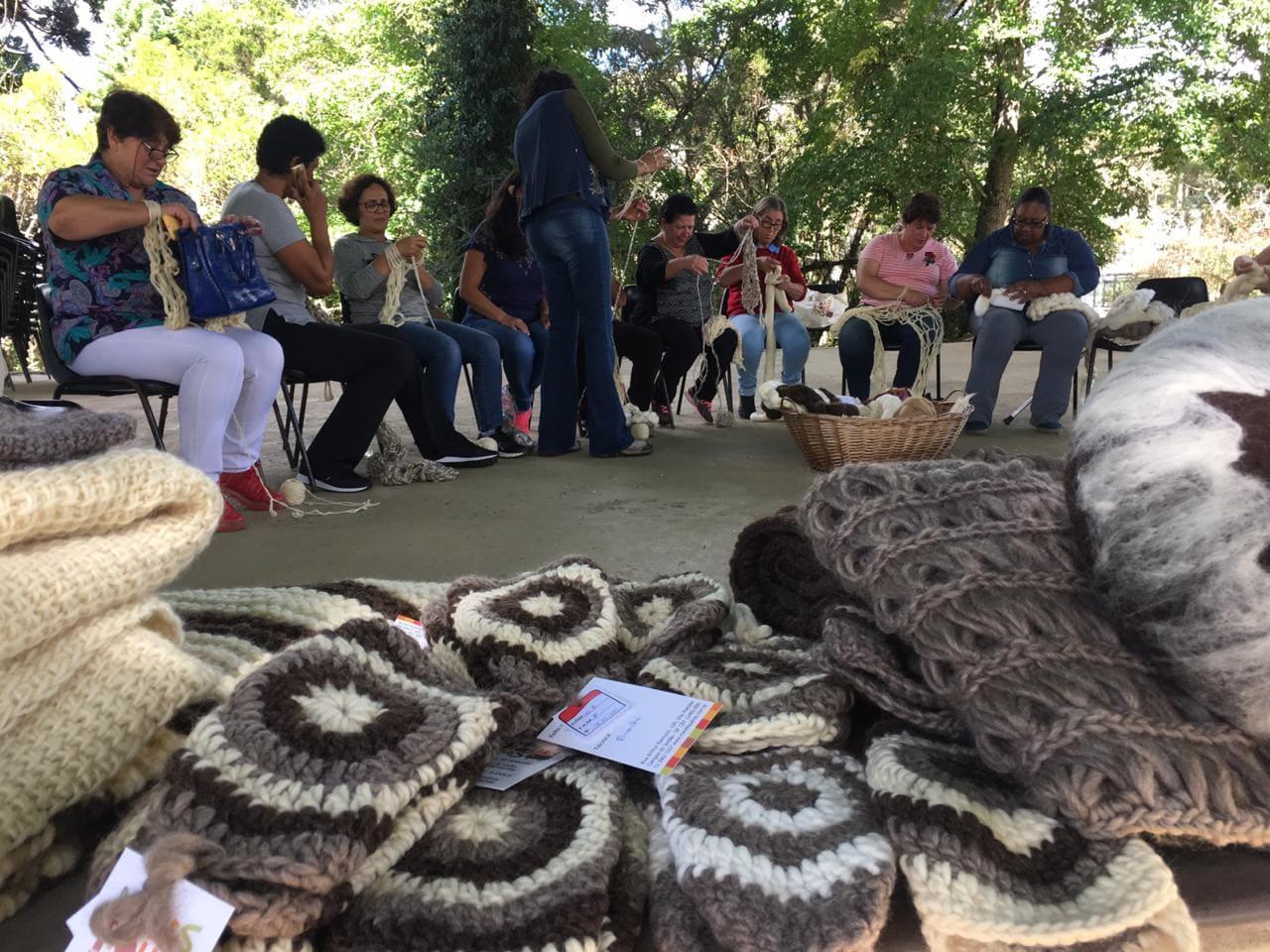 Um grupo de mulheres está sentado em cadeiras que formam um semicírculo. Elas estão com linha e agulhas na mão tricotando, enquanto uma mulher esta me pé mostrando detalhes de como se trabalha com a lã.