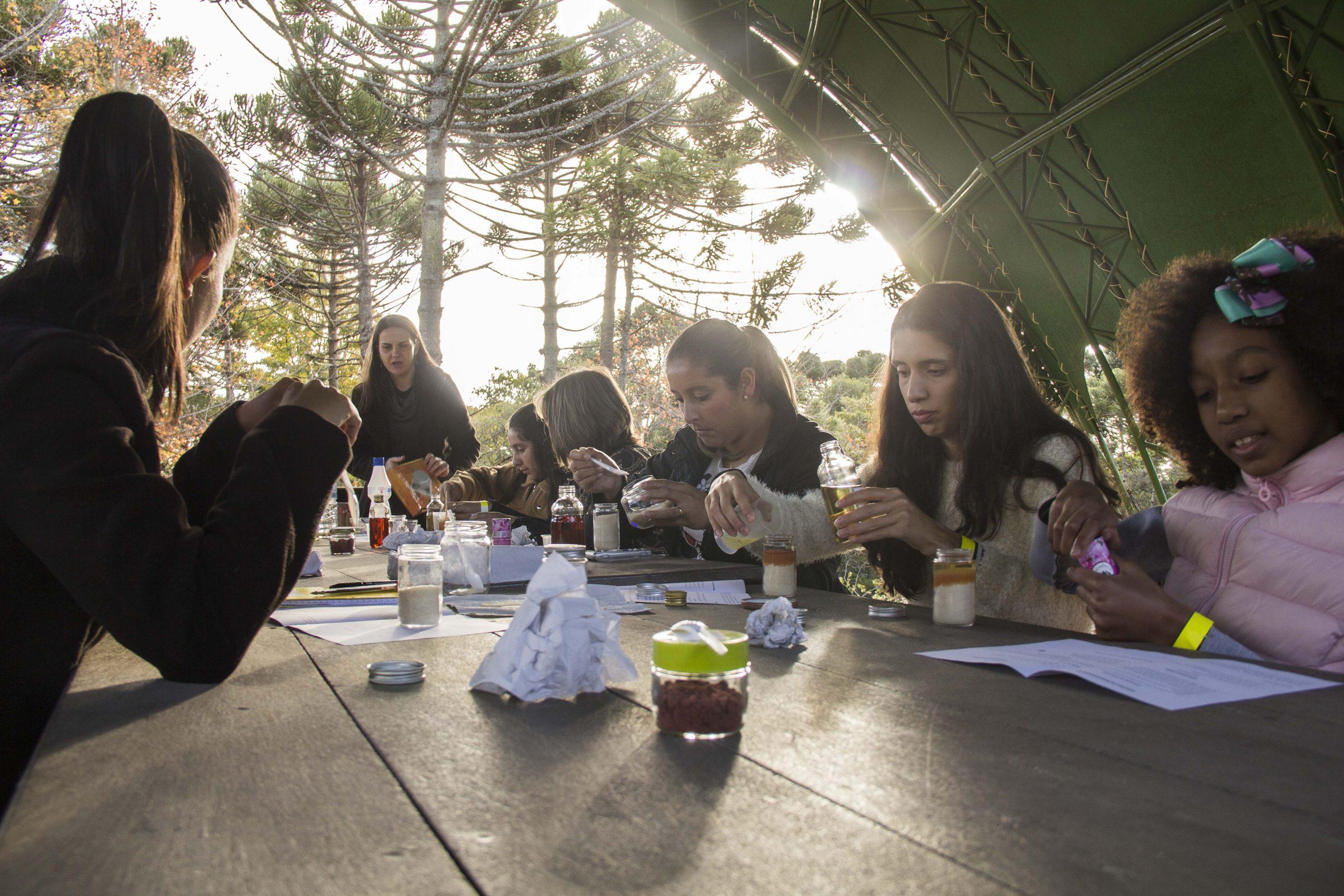Numa mesa retangular estão sentadas seis mulheres, sendo elas brancas e negras. Sobre a mesa há algumas folhas e potes de vidro na qual elas fazem o manuseio. Um mulher em pé ao redor da mesa faz a instrução as demais.
