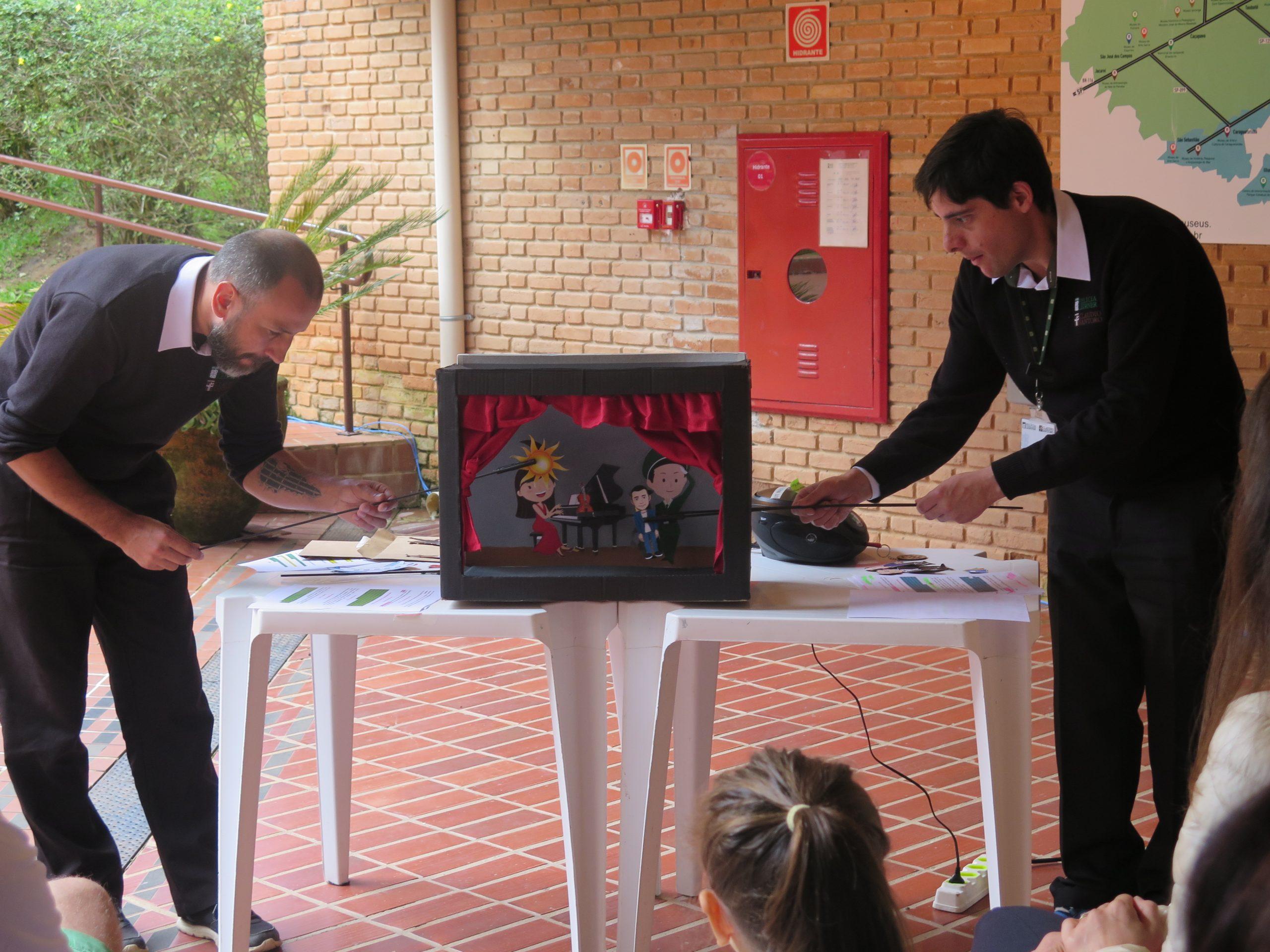 Dois educadores estão apresentando o teatro de papel da história de Claudio Santoro.
