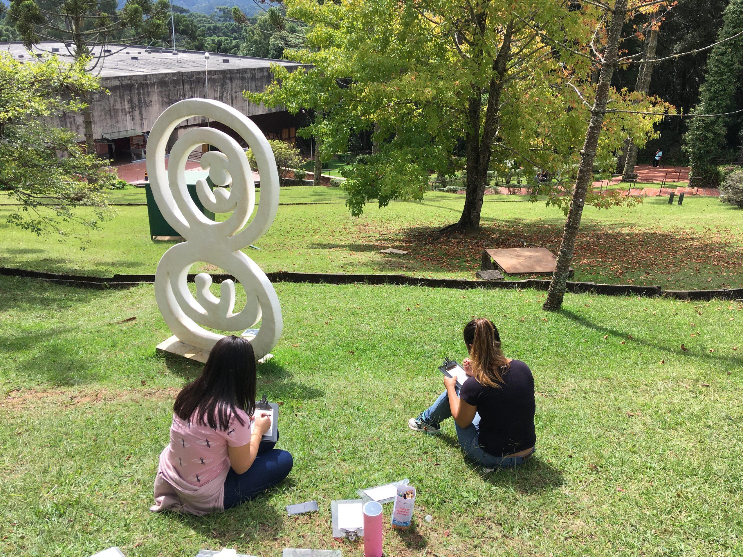 """Duas mulheres estão sentadas próxima a escultura """"Nascimento"""" e estão realizando uma atividade com uso de prancheta e lápis coloridos."""