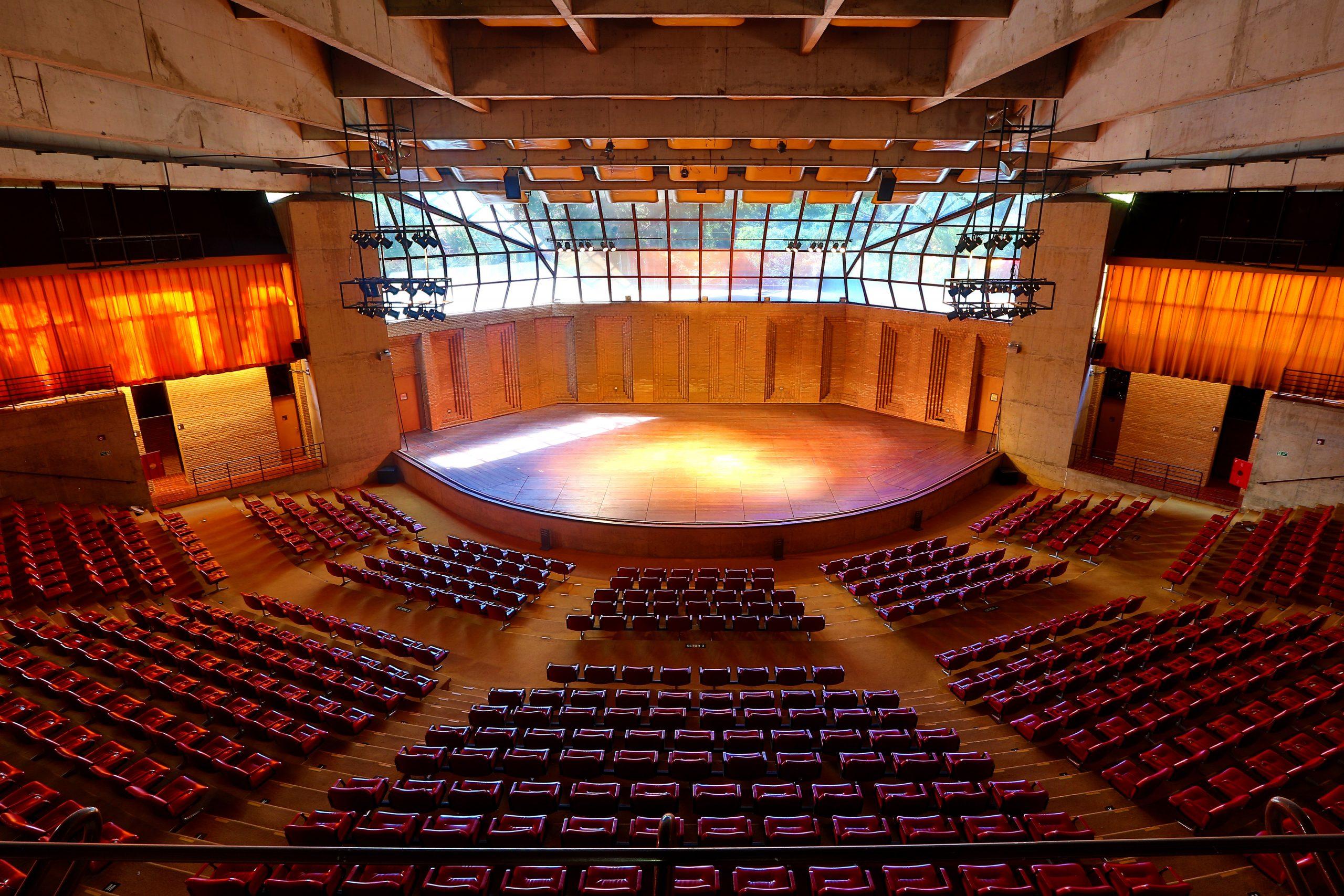 A imagem mostra o Auditório Claudio Santoro que possui uma arquitetura que se assemelha a arena. Há diversas poltronas na cor vermelha, um palco com luzes e vidraças nas quais é possível observar a natureza.