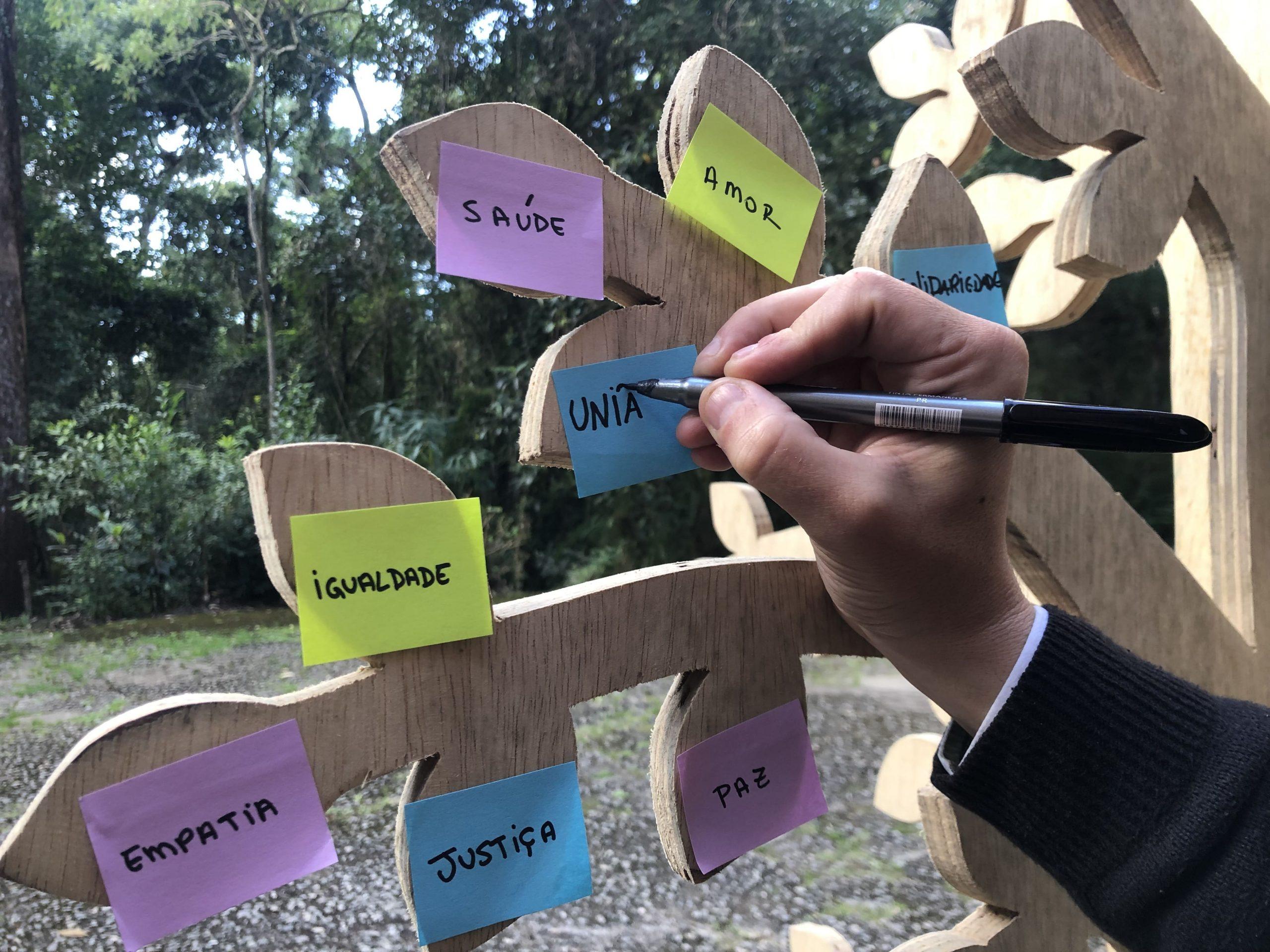 Na imagem, há galhos de uma árvore feita de madeira onde estão colados diversos post-it com palavras como: igualdade, empatia, saúde, amor. Uma mão está segurando uma caneta e escreve em um dos post it a palavra união.
