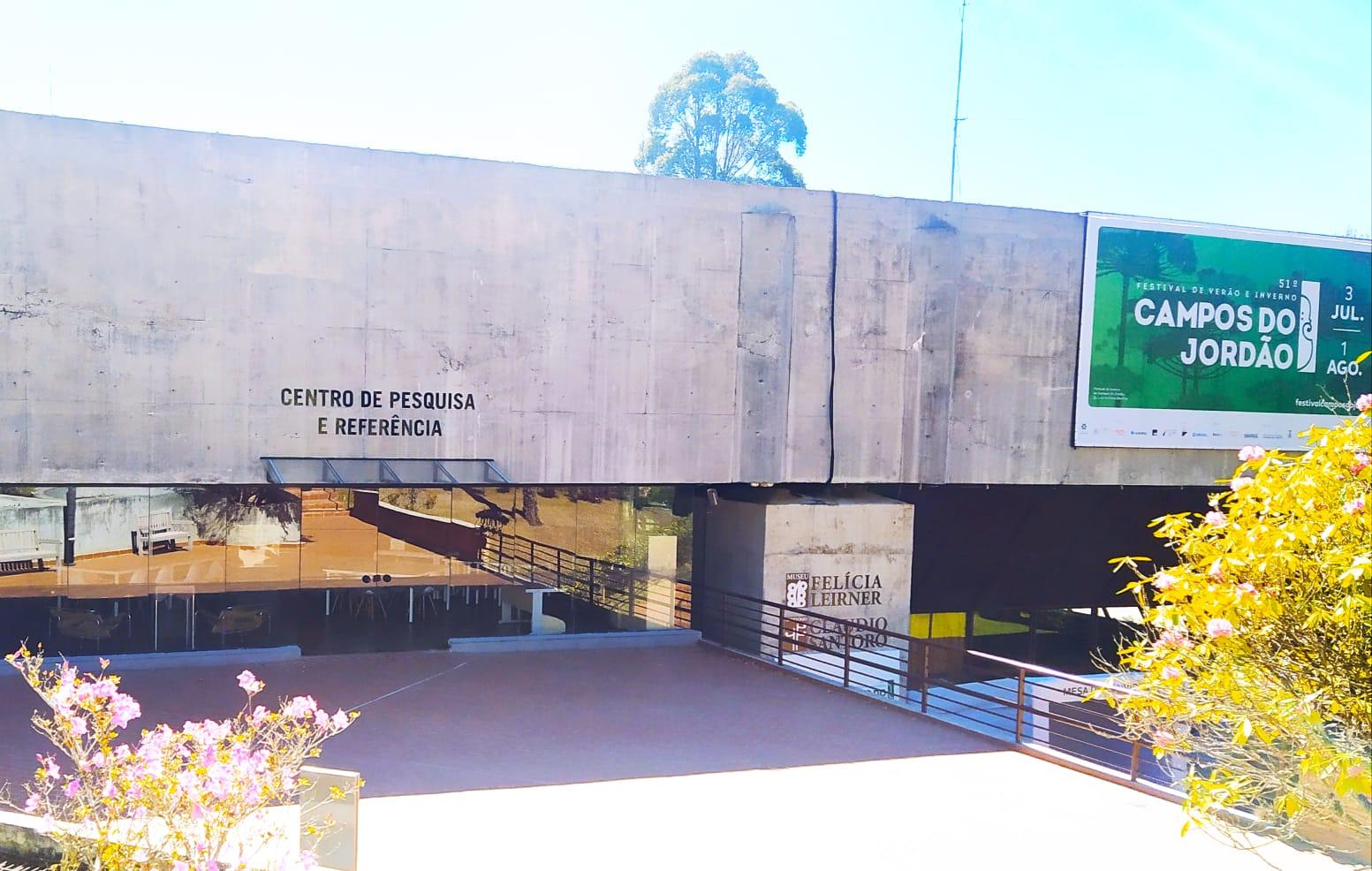 A imagem mostra a entrada do Centro de Pesquisa e Referência que contém uma arquitetura robusta com uma fachada em vidro.