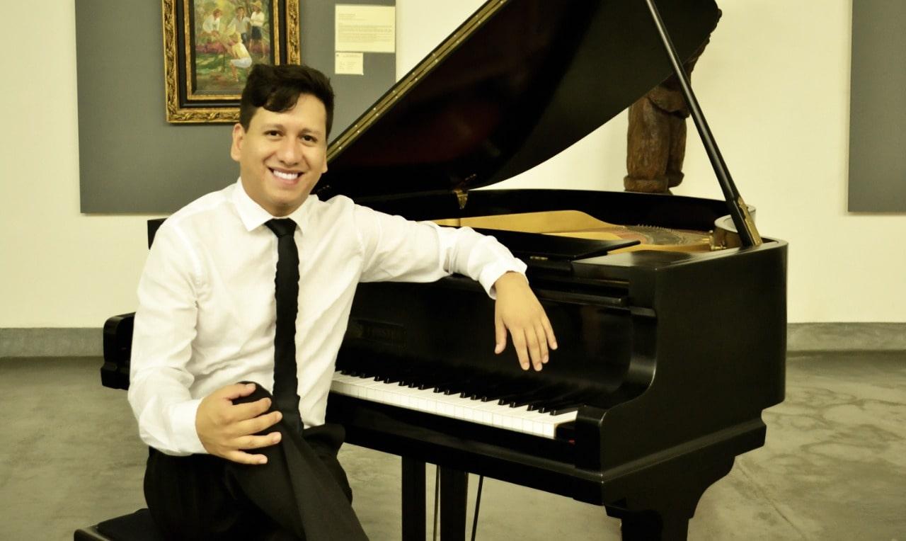 Um homem branco, de cabelos castanhos está usando uma camisa branca e uma gravata preta. Ele está sentado de frente com um piano de calda, apoiando um dos braços sobre o instrumento.
