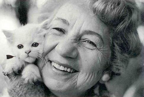 A imagem está preto e branco e há uma mulher idosa de cabelos curto e cacheados. Ela segura próximo ao seu rosto um filhote de gato.
