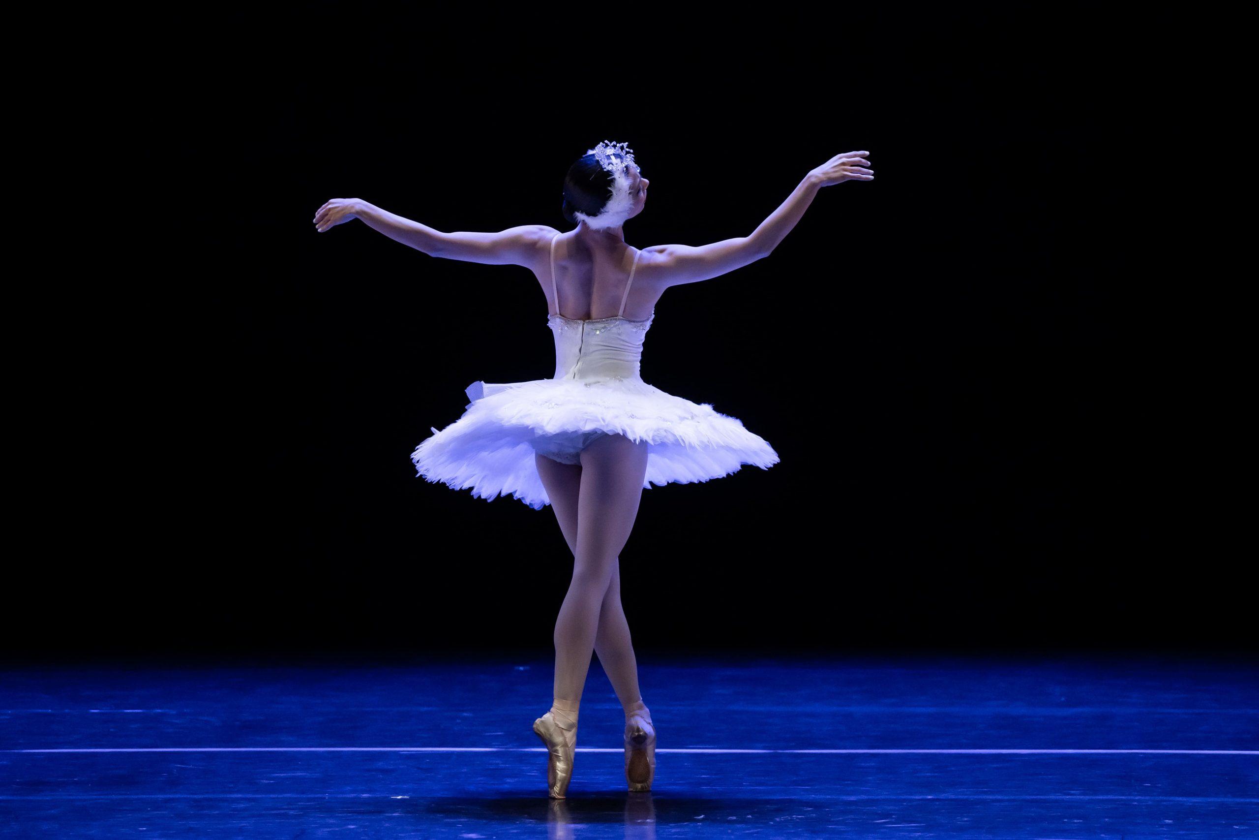 Uma bailarina está de costas e faz um movimento de ballet.