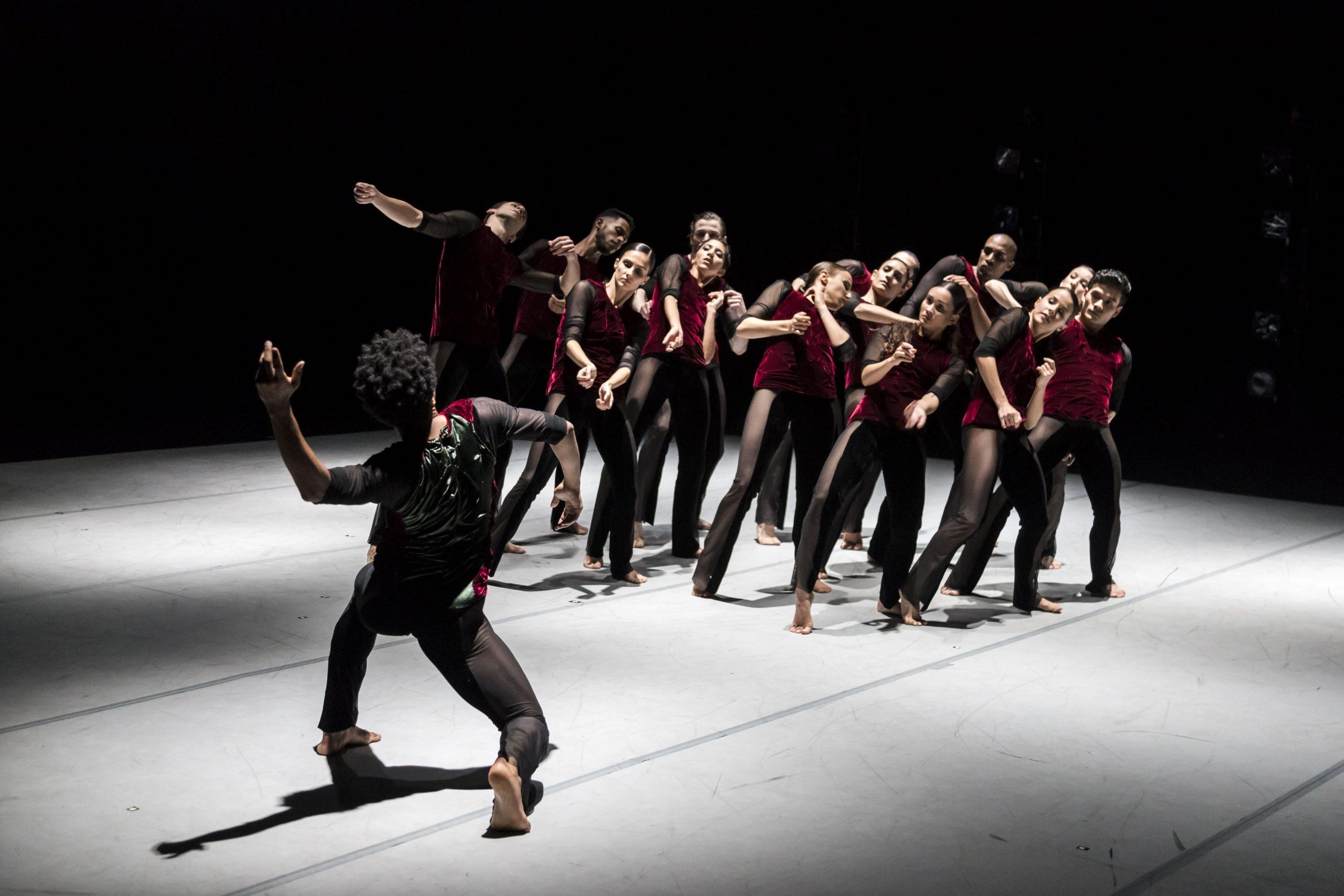 A imagem mostra um grupo de bailarinos dançando sobre um palco. Eles usam uma camiseta vermelha e uma calça preta.